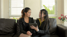 Young Asian Businesswomen Discussing Work on a Tablet Computer Footage