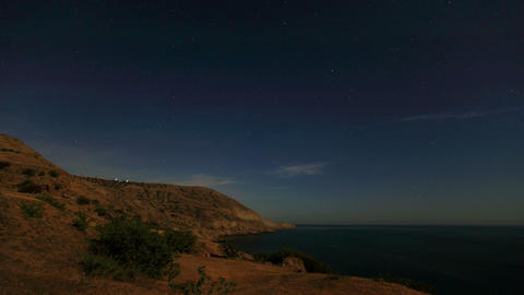 Night landscape, night sky with moving stars over the sea. Mountain Meganom, Crimea, Ukraine (time l Footage