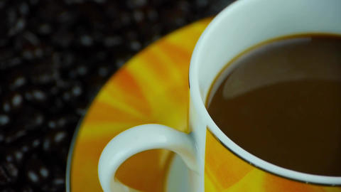 rotating a cup of coffee & coffee beans background,top view Footage