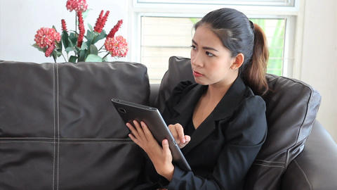 Asian Female Office Worker Using Tablet On Sofa Footage