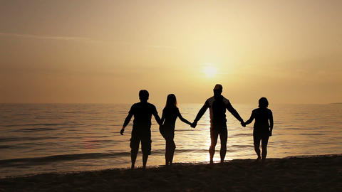 Four friends jumping on the beach at sunset Stock Video Footage