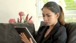 Young Asian Woman Thinking While Using a Tablet Computer Stock Video Footage
