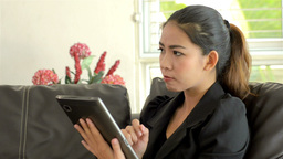 Young Asian Woman Thinking While Using a Tablet Computer Footage