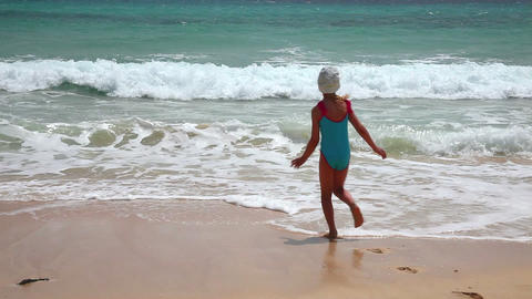 Cute young girl having fun with sea waves on beach Footage