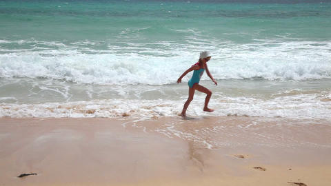 Cute young girl having fun with sea waves on beach Stock Video Footage