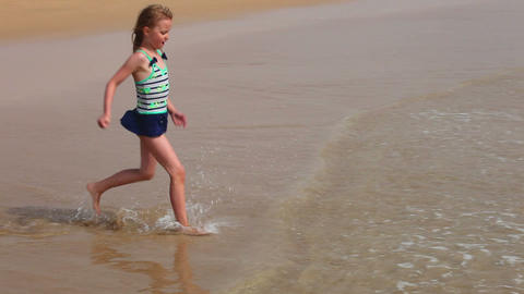 Young girl playing with sea waves on the beach Stock Video Footage