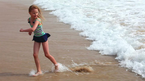 Young girl playing with sea waves on the beach Footage