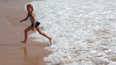 Young girl having fun with sea waves on the beach Footage