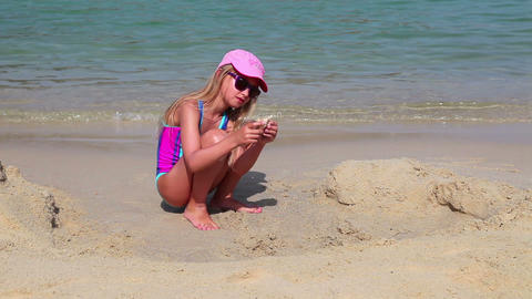 Young girl found sea shell in sand of the beach Stock Video Footage