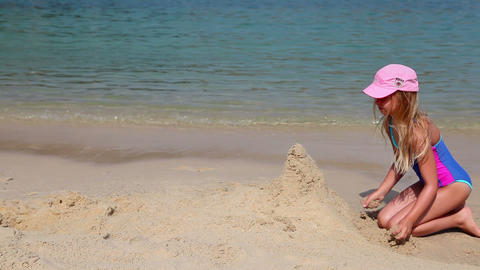 Young girl builds a sand castle on the beach Stock Video Footage