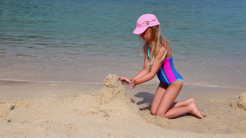 Young girl builds a sand castle on the beach Footage