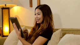 Young Asian Woman Video Chatting on Her Tablet in Her... Stock Video Footage