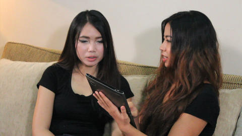 Asian Woman Shows Friend How To Use PC Tablet Stock Video Footage