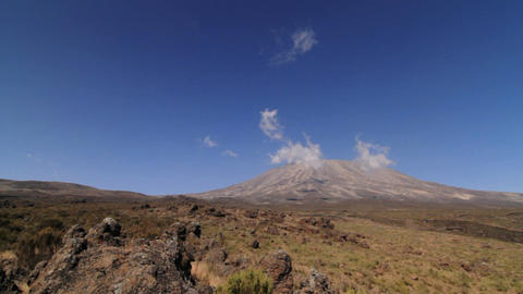 Wide shot of Kilimanjaro with trekker walking into frame Stock Video Footage