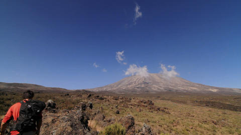 Wide shot of Kilimanjaro with trekker walking into frame Footage