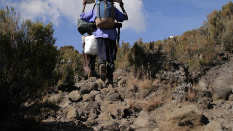 Porters carrying gear down trail Stock Video Footage