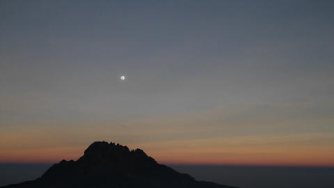 Moon over rocky outcrop at sunset Footage