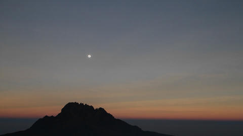 Moon over rocky outcrop at sunset Stock Video Footage
