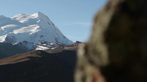 Pan from behind rock revealing snowy peak Stock Video Footage