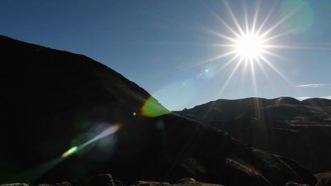 Sun burst with snowy peak in the background Stock Video Footage
