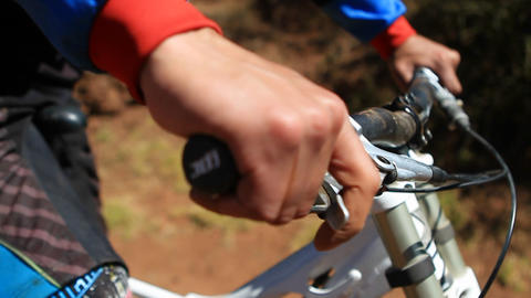 Biking with hands on grip checking breaks Footage