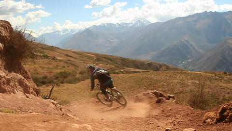 Wider pan as bike goes down trail, hills in back Stock Video Footage