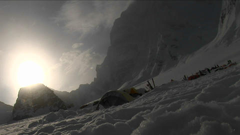 Snow falling through sun onto camp Stock Video Footage