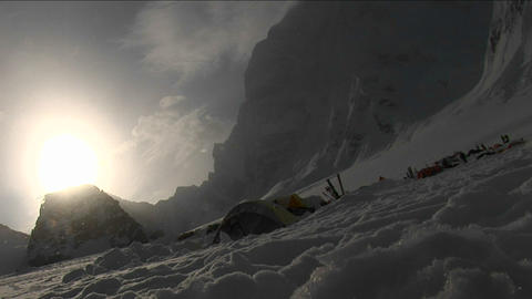 Snow falling through sun onto camp Stock Video Footage