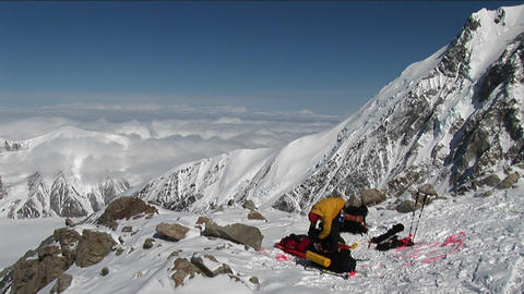Climber packing bags high on Denali Footage