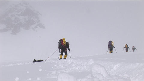 Snow falling on climbers as they struggle Stock Video Footage