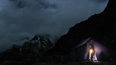 Tent lite up at camp at night, climbers in and out Stock Video Footage