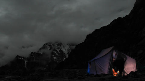 Tent lite up at camp at night, climbers in and out Live Action