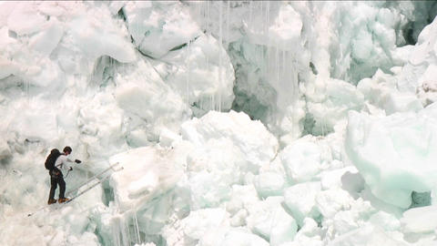 Climber crossing ladder in icefall Stock Video Footage