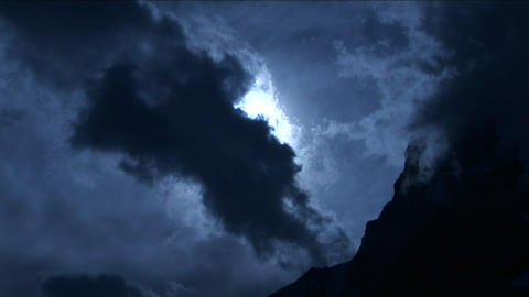 Pan onto peak in pale blue light with clouds Stock Video Footage