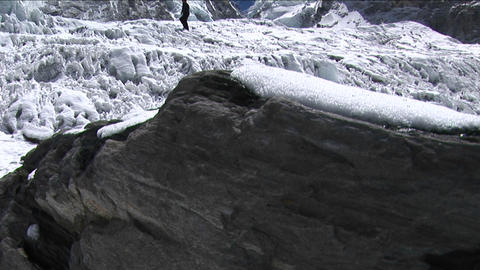 Pan from rock revealing climber near icefall Stock Video Footage