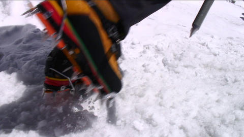 Crampons digging into snow as climber ascends Stock Video Footage
