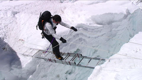 Climber on ladder looking down at crevasse Stock Video Footage