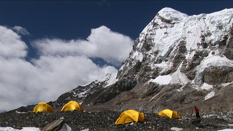 Climber walking to and entering tent under Pumori Footage