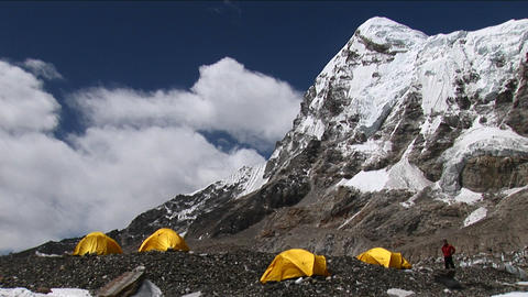 Climber walking to and entering tent under Pumori Stock Video Footage