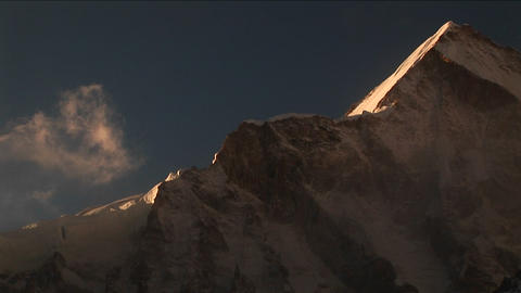 Clouds drifting behind backlit mountain Stock Video Footage