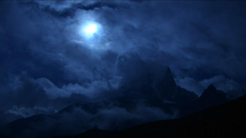 Pan of clouds over summit in blue light Stock Video Footage