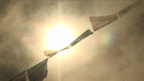 Zoom in through smoke at prayer flags and sun Stock Video Footage