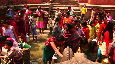 Women waiting to fill up water at community taps Stock Video Footage