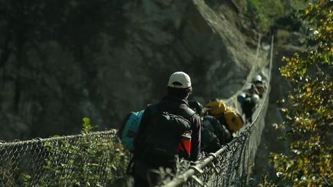 Focus shift to Yaks crossing bridge loaded with gear Stock Video Footage