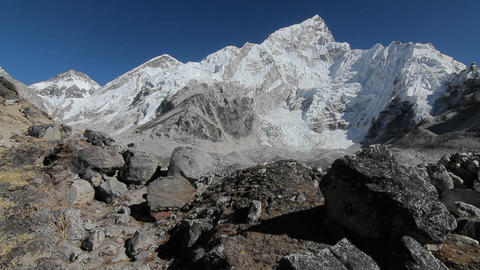 Glide of Nuptse from behind rocks Stock Video Footage