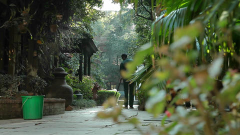 Glide to reveal man sweeping at Kathmandu hotel Footage