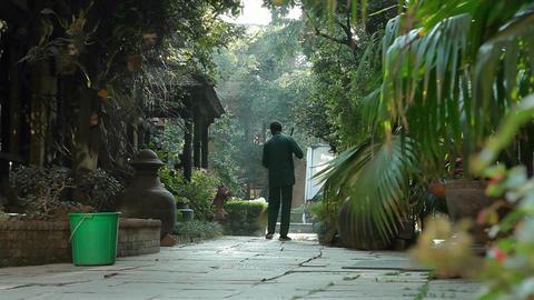 Glide to reveal man sweeping at Kathmandu hotel Stock Video Footage