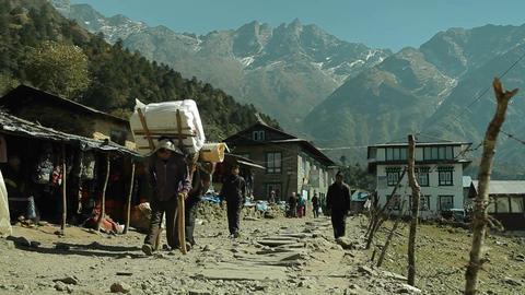 Porters walking down trail in Lukla Footage