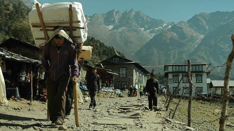 Porters walking down trail in Lukla Stock Video Footage