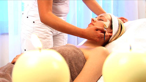 Young blonde girl having facial skin mask applied at beauty spa with candles in foreground Footage